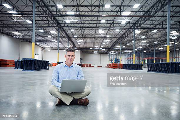 Caucasian businessman using laptop in empty warehouse