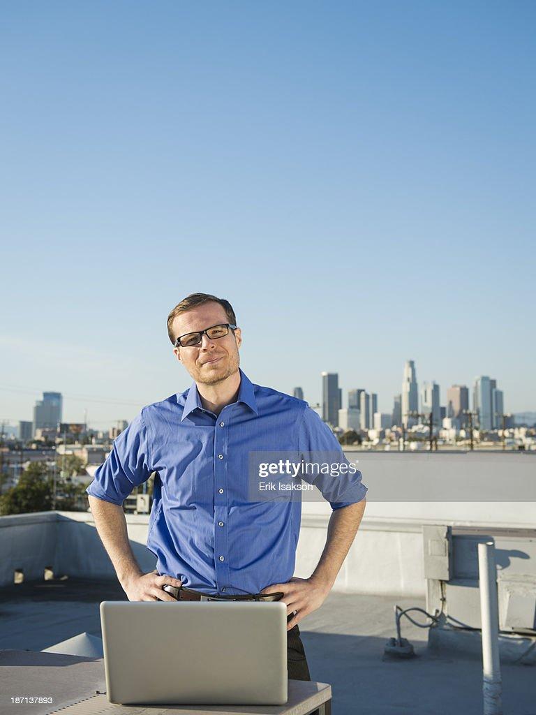 Caucasian businessman using laptop on urban rooftop : Stock Photo