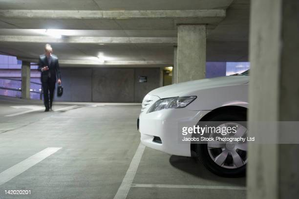Caucasian businessman walking in parking garage