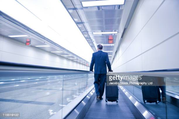 Caucasian businessman walking on moving walkway in airport