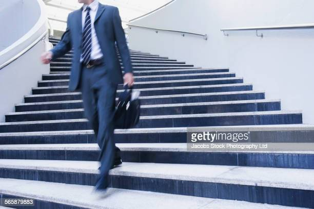 Caucasian businessman walking on staircase