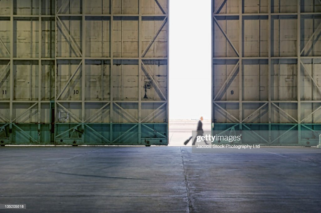 Caucasian businessman walking past warehouse doors