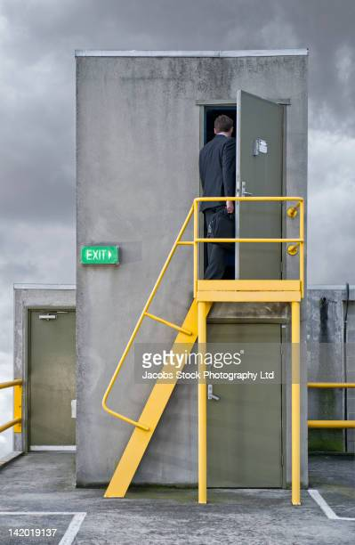Caucasian businessman walking through rooftop doorway