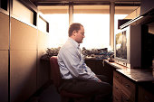 Caucasian businessman watching television at desk