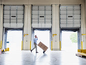 Caucasian businessman wheeling cardboard boxes in warehouse