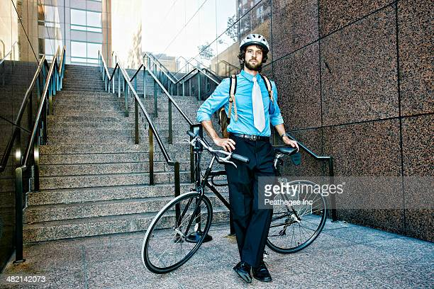 Caucasian businessman with bicycle on urban stairs