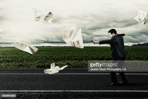 Caucasian businessman with newspaper on windy remote road