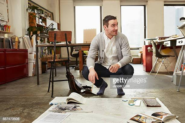 Caucasian businessman working on floor in office