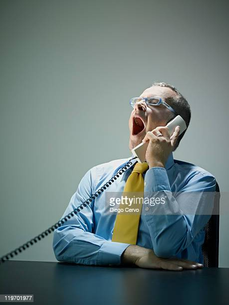 Caucasian businessman yawning and talking on telephone