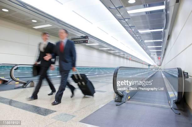Caucasian businessmen rushing in airport