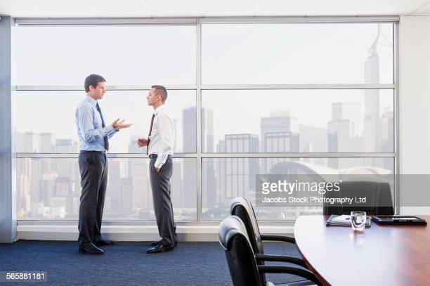 Caucasian businessmen talking near office window