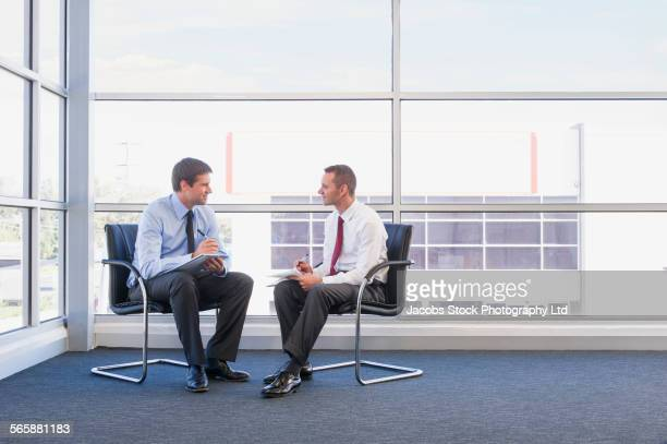 Caucasian businessmen talking near office window