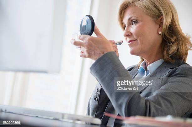 Caucasian businesswoman applying makeup in office