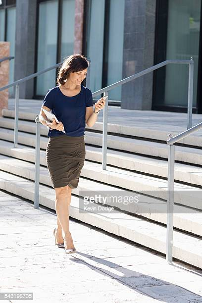 Caucasian businesswoman carrying cell phone and digital tablet outdoors