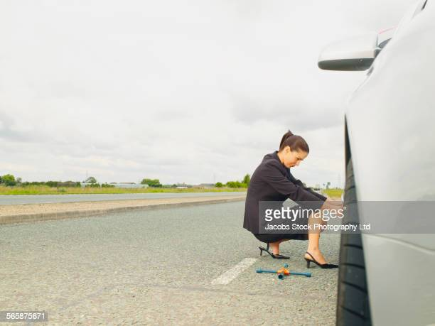 Caucasian businesswoman changing car tire on rural road