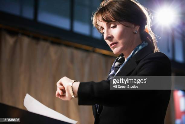 Caucasian businesswoman checking the time
