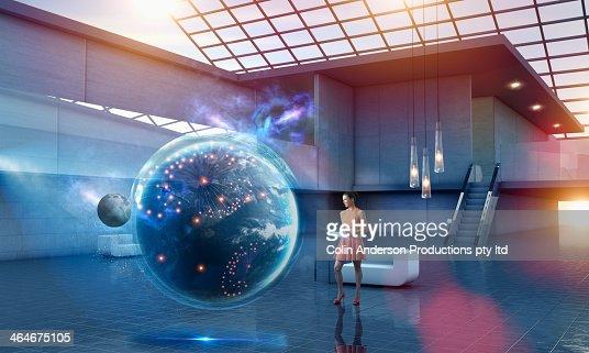 Caucasian businesswoman examining virtual globe