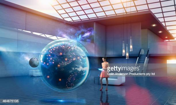 Caucasian businesswoman examining virtual globe