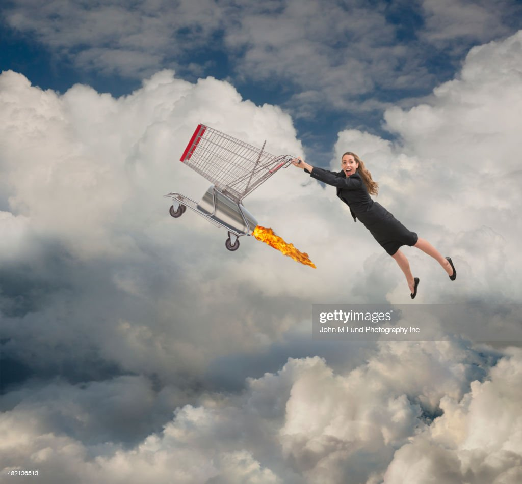 Caucasian businesswoman flying on shopping cart in clouds : Stock Photo