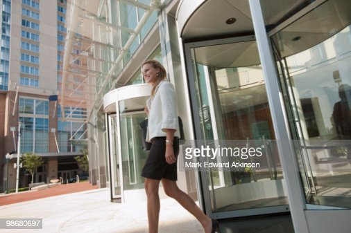 Caucasian businesswoman leaving office building : Stock Photo