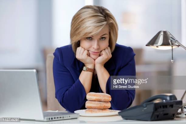 Caucasian businesswoman looking at stack of donuts