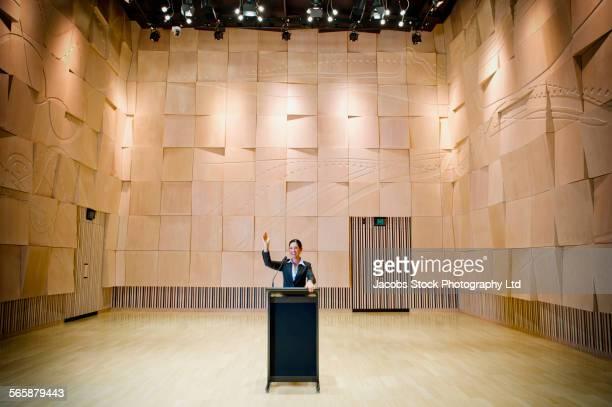 Caucasian businesswoman raising hand at podium