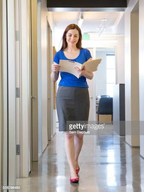 Caucasian businesswoman reading folder in office hallway