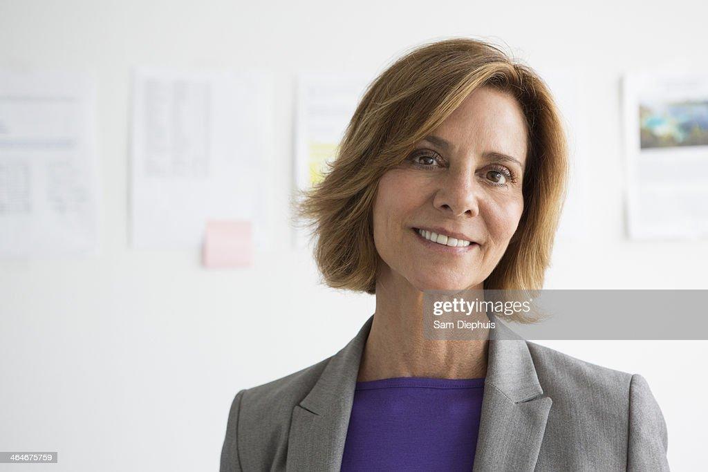 Caucasian businesswoman smiling in office