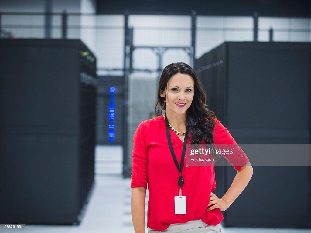 Caucasian businesswoman smiling in server room