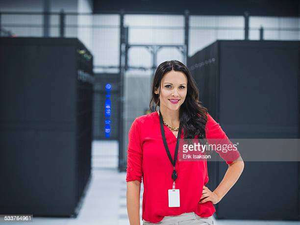 Caucasian businesswoman smiling in server room