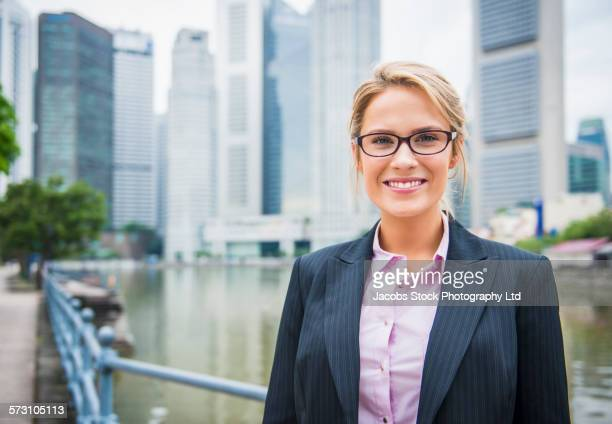 Caucasian businesswoman smiling on Singapore waterfront