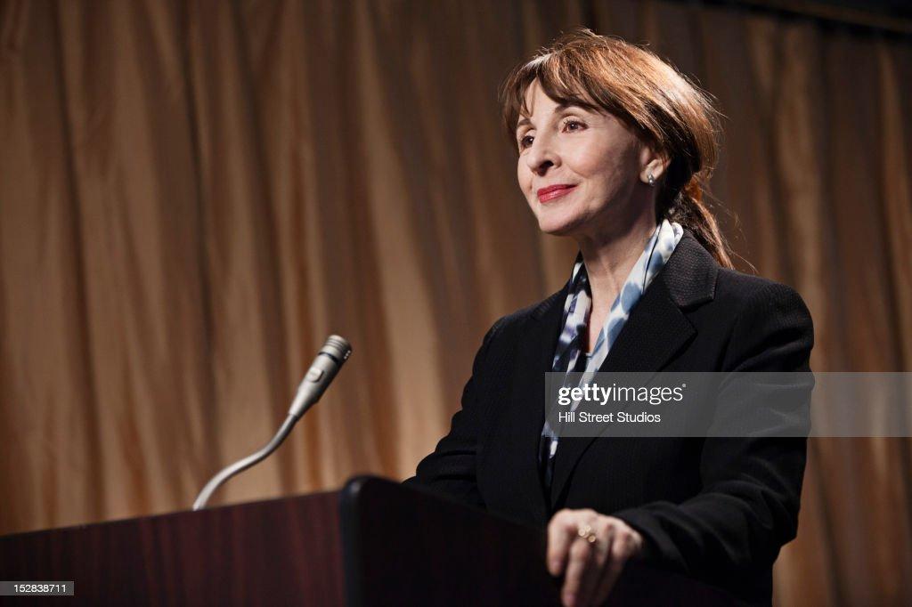 Caucasian businesswoman standing at podium : Stock Photo
