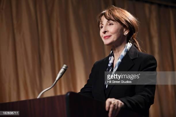 Caucasian businesswoman standing at podium