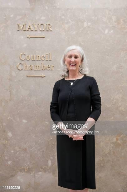 Caucasian businesswoman standing in office corridor