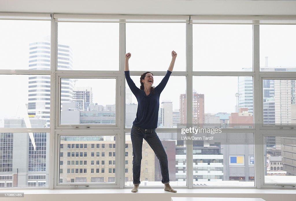 Caucasian businesswoman standing on windowsill
