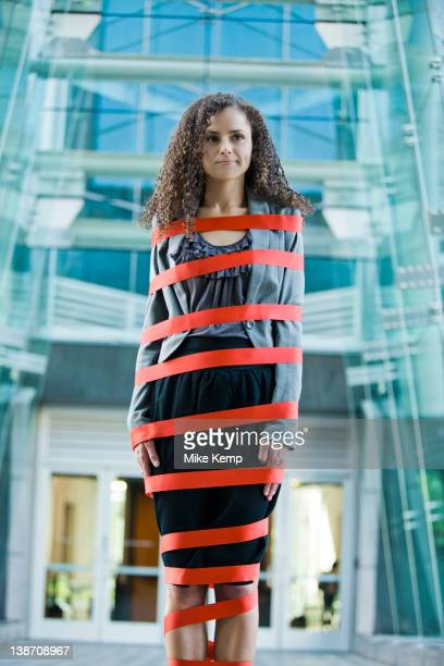 Caucasian businesswoman standing wrapped in red tape