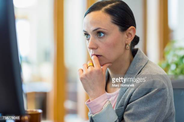 Caucasian businesswoman staring at computer in office