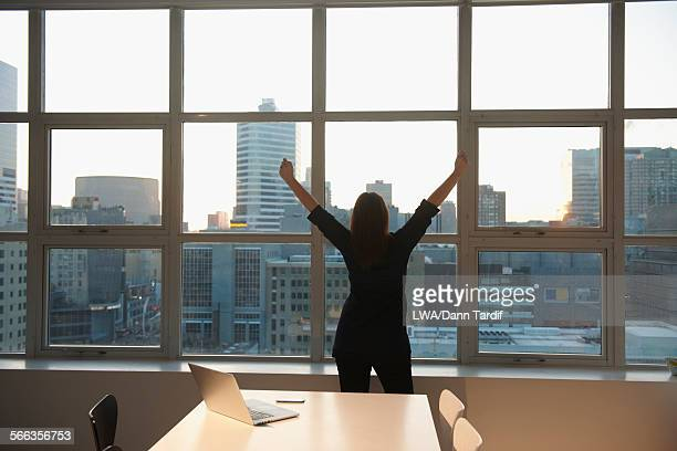 Caucasian businesswoman stretching at office window
