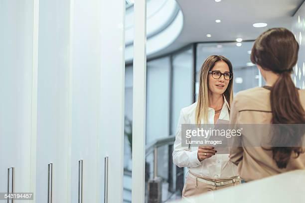 Caucasian businesswoman talking in office corridor