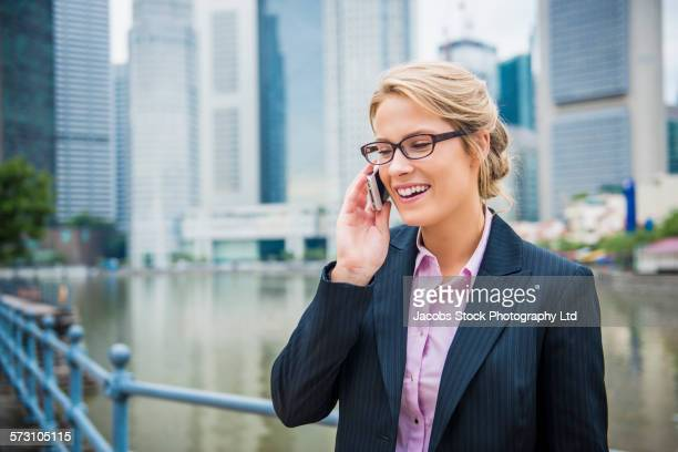 Caucasian businesswoman talking on cell phone on Singapore waterfront