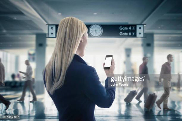 Caucasian businesswoman text messaging on cell phone in airport