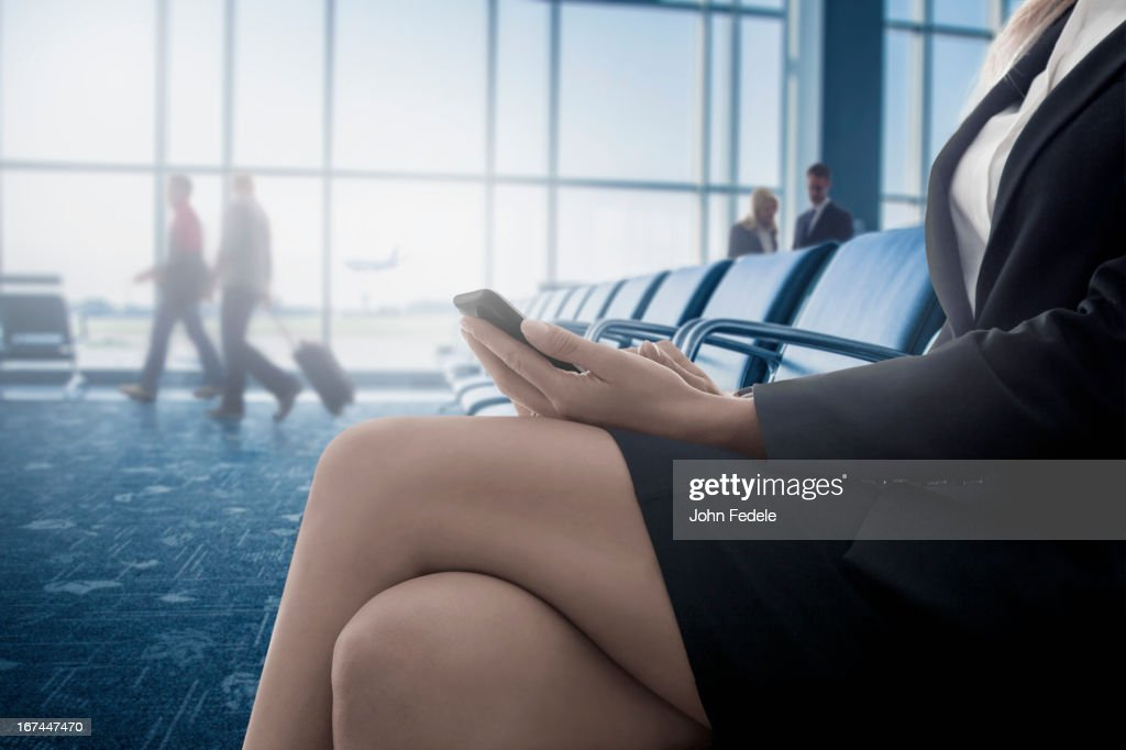 Caucasian businesswoman text messaging on cell phone in airport : Stock Photo