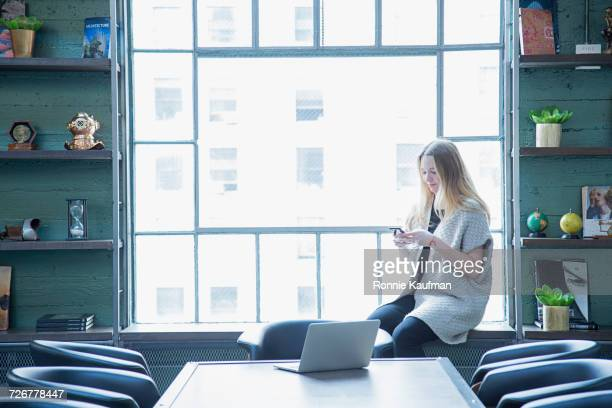 Caucasian businesswoman texting on cell phone on window sill in office