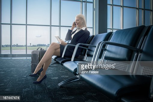 Caucasian businesswoman using cell phone and digital tablet in airport : Stock Photo