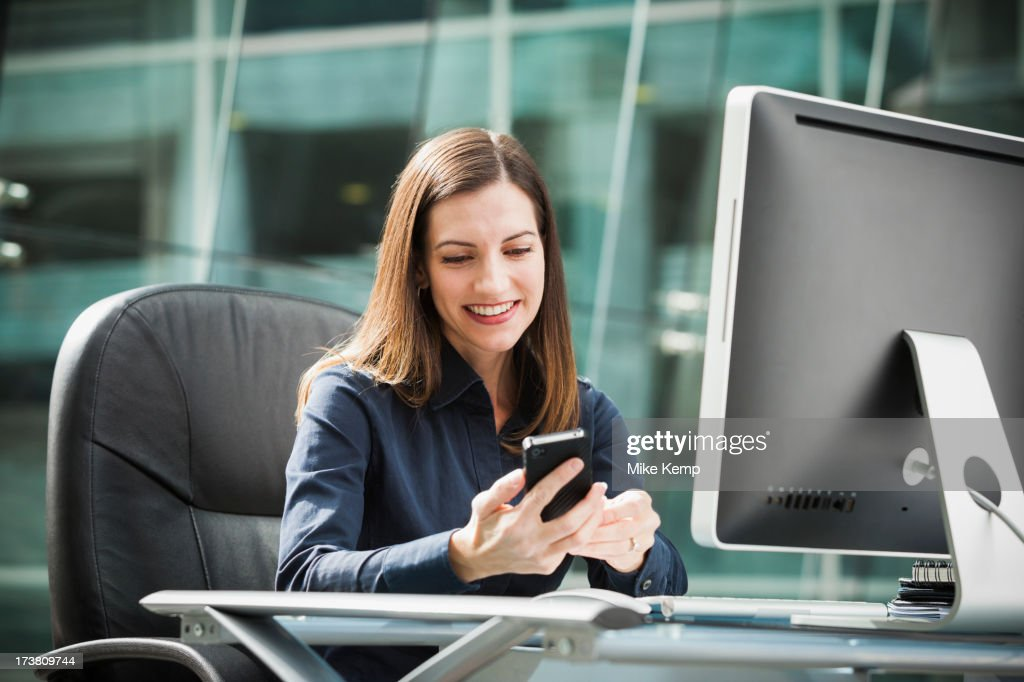 Caucasian businesswoman using cell phone at desk : Stock Photo