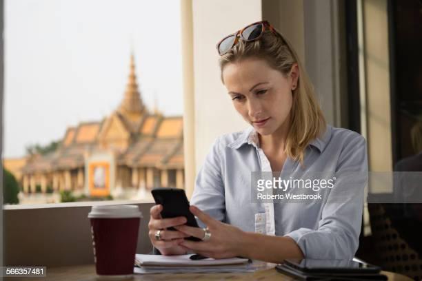 Caucasian businesswoman using cell phone in cafe, Phnom Penh, Cambodia
