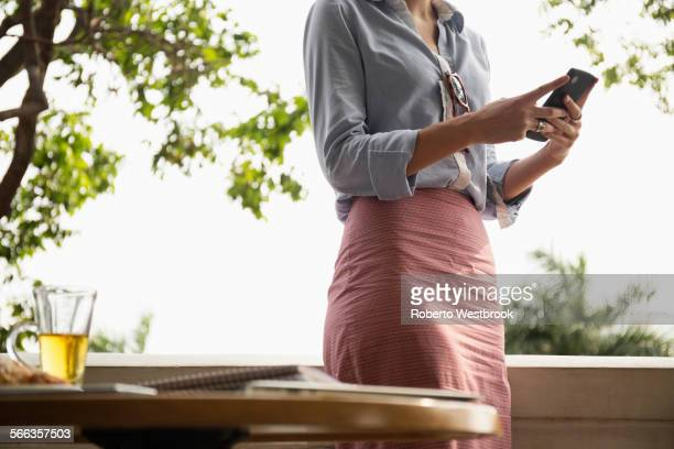 Caucasian businesswoman using cell phone on balcony