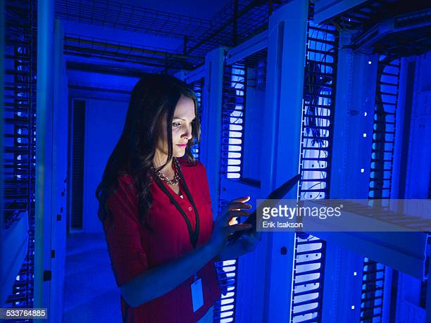 Caucasian businesswoman using digital tablet in server room