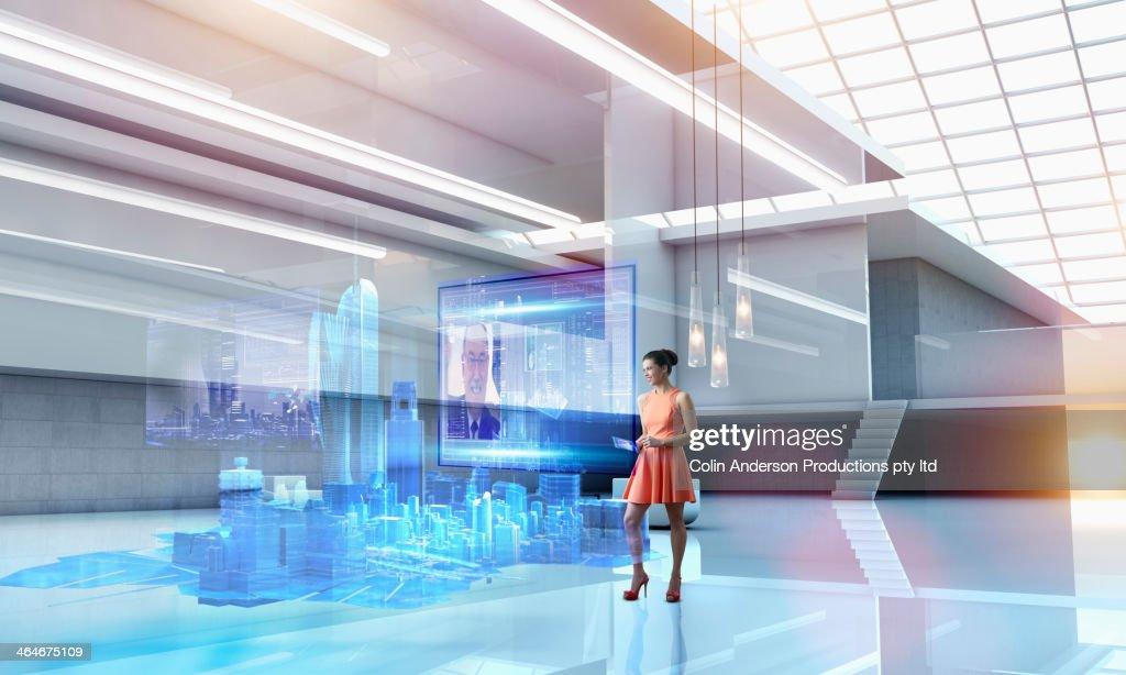 Caucasian businesswoman using hologram computer screen : Stock Photo