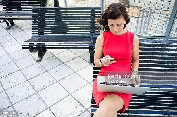 Caucasian businesswoman using laptop and cell phone on bench